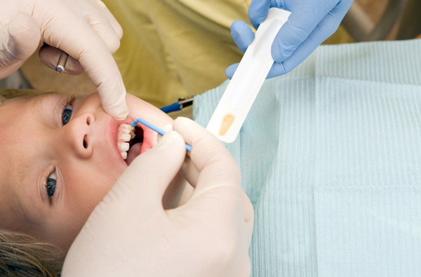 Young boy receiving fluoride treatment at dentist